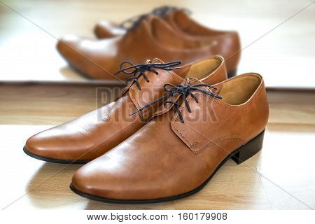 Classic brown lace up leather male dress shoes placed next to the mirror on a wooden floor. Timeless oxford desing smooth toe fine stitching all-leather construction