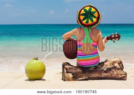 Little happy baby in rastaman hat have fun play reggae music on Hawaiian guitar enjoy relaxing on ocean beach. Children healthy lifestyle. Travel family activity on tropical island summer holiday