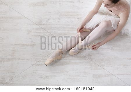 Beautiful legs of young ballerina who puts on pointe shoes at white wooden floor background, top view from above with copy space. Ballet practice. Beautiful slim graceful feet of ballet dancer.