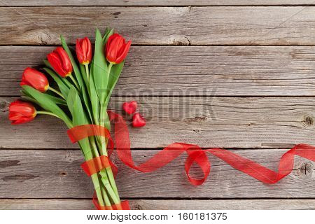 Red tulips and candy hearts over wooden table. Top view with copy space