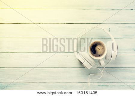 Headphones and coffee cup on wooden table. Music concept. Top view with copy space