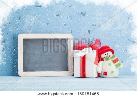 Christmas chalkboard, snowman and gift box. View with copy space for your text