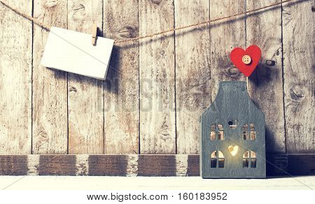Valentine's day home or love concept. Piece of paper with wooden clamp on rope with wooden home horizontal