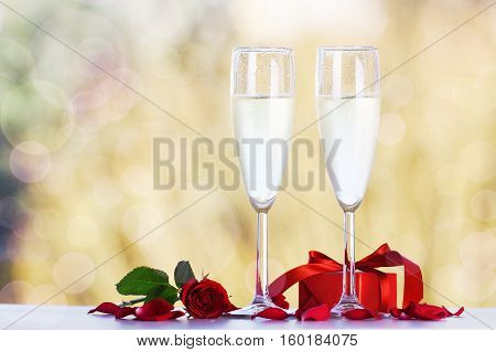Couple glasses of champagne with beautiful red roses and gift on bright bokeh background. Love valentine's day or celebrating concept