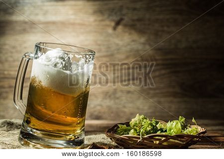 Big tankard of beer standing on empty wooden background with hops on table