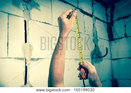 Worker with yellow tape measure in centimeters and feets measure the distance to the newly built walls from bricks - retro style