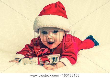 Funny Santa Baby Girl Lying On White Blanket With Gift