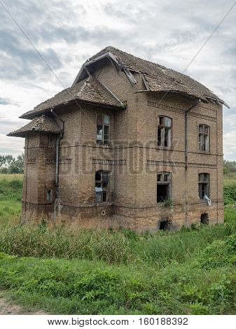 Picture of an old abandoned mansion-house. Verdurous mansion against the background of cloudy sky. Old mansion made of brown bricks. The windows of the mansion are broken.