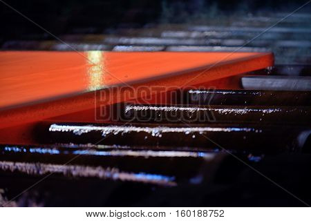 Hot steel plate on conveyor, close up