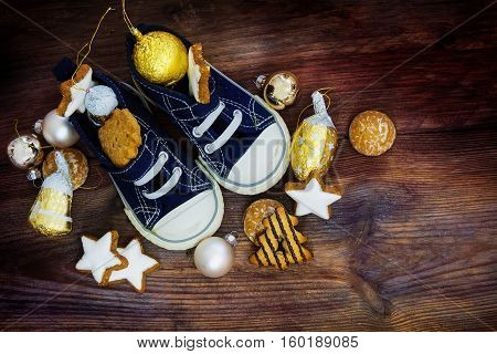 Childrens shoes filled with sweets cookies and christmas decoration for Nicholas day on the 6th December in Germany on rustic wood view from above copy space