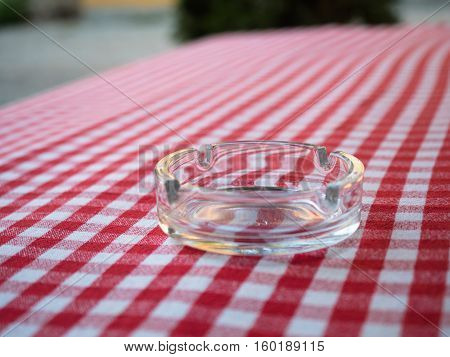 Selective focus on the ashtray laying on the table cloth with a pattern of red and white squares. Glassy ashtray against blurred background of the table cloth texture.