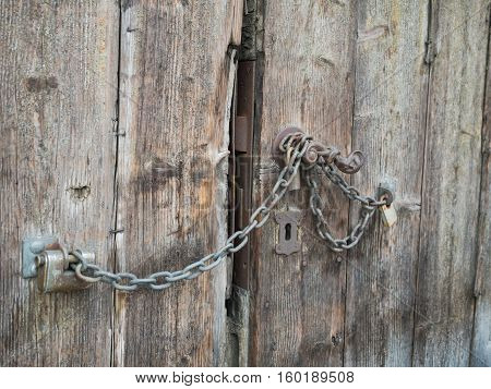 Picture of an old wooden gate closed with rusty chain. Background of the old batten door. Rusty padlock on the old door. An old planking of the gate.