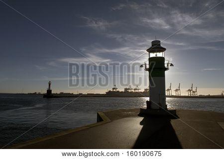 AARHUS DENMARK - NOVEMBER 24 2016: Portside lighthouse in the port of Aarhus. Container Port is the largest in Denmark seen in the background November 24 2016