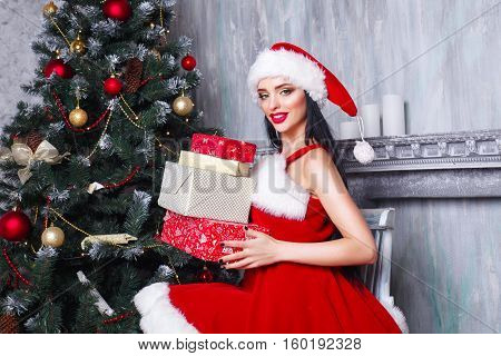 beautiful sexy girl wearing santa claus clothes . Smiling woman with big and small gift. Women on dress and santa's hat. Santa's helper