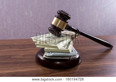 Judge gavel with dollars on wooden table