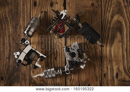 Three Tattoo Guns Arranged On A Brown Wooden Table