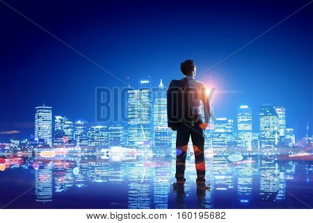 Businessman thinking and looking at night city . Mixed media