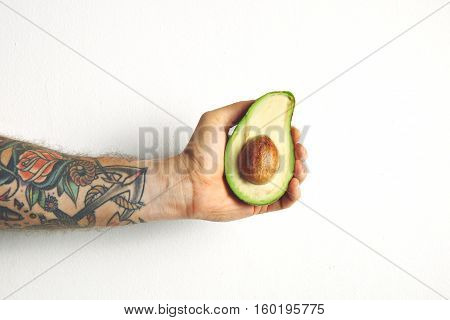 Close up shot of a man's hand holding a large greenish white avocado cut in half with stone inside