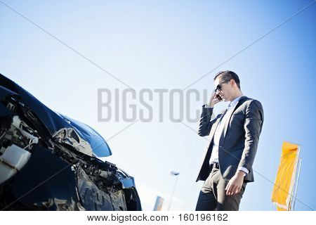 close-up of male adult man in suit, businessman, dealer checking damaged crashed black car after car accident, sunny daytime, winter