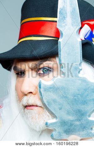 Frown senior man bearded beefeater yeomen warder or male royal guard bodyguard in hat with spear on grey wall