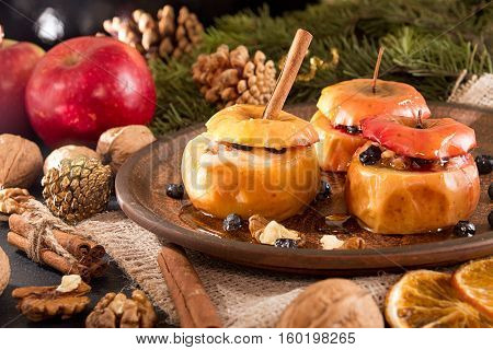Baked apples on brown plate with holiday Christmas decoration with Christmas tree branch cones cinnamon walnuts and red apple.