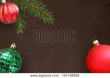 Dark background with Christmas fir branch red wavy dull and green ribbed ball. Top view.