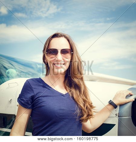 Young smiling woman standing near private plane ready for flight. Warm color toned image. Aviation school background