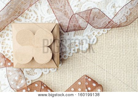 Vintage brown paper gift box with ribbon on burlap sack background.
