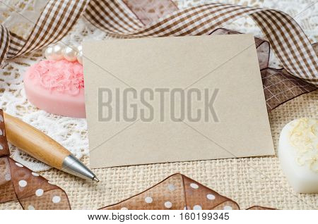 Blank note paper and pen decorated with brown ribbon on burlap sack background