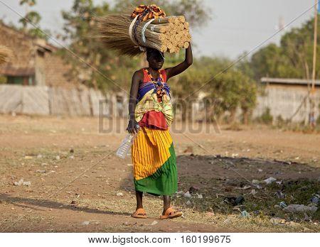 TORIT, SOUTH SUDAN-FEBRUARY 20 2013: Unidentified woman carries heavy load on her head in Torit, South Sudan.