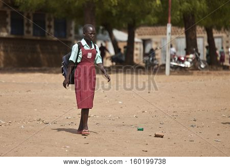 TORIT, SOUTH SUDAN-FEBRUARY 20 2013: Unidentified female student leaves the primary school in Torit, South Sudan