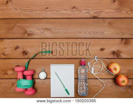 Healthy lifestyle concept. Apple dumbbell water stopwatch measuring tape and headphones on rustic wooden table.