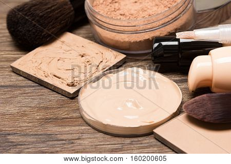 Foundation makeup products: liquid and cream foundation, concealer, powder, professional makeup brushes. Selective focus