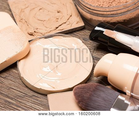 Foundation makeup products: liquid and cream foundation, concealer, powder, cosmetic sponge, professional flat brush. Selective focus