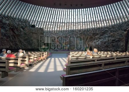 Helsinki, Finland - April 10, 2010: People sit on the benches in Temppeliaukio Church (Church of the Rock) on Lutherinkatu. Was built directly into solid rock and opened in 1969