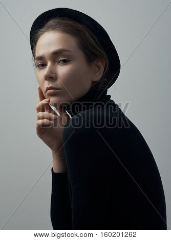 Dramatic Portrait Of A Young Beautiful Girl With Freckles In A Black Turtleneck And A Hat On Her Hea