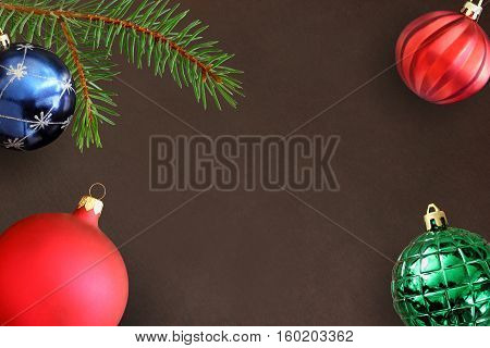 Dark background with Christmas fir branch blue green ribbed and red wavy dull ball