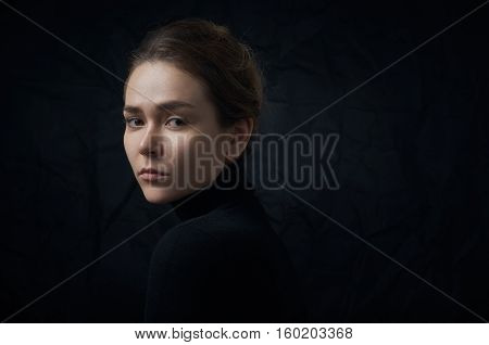 Dramatic Portrait Of A Young Beautiful Girl With Freckles In A Black Turtleneck On Black Background
