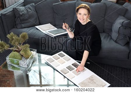 Interior decorating, shopping carpet. Arranging home shopping coverings. Woman chooses carpet for the living roomInterior designer with the probe carpets