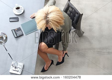 The woman writes in a notebook. Young attractive girl sitting at a desk recorded. Household bills. Female summarizes expenses