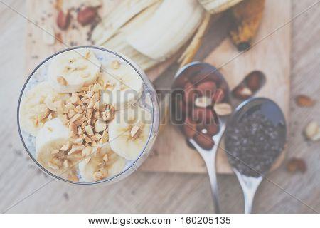 Banana chia yogurt pudding decorated with ripe sliced banana and peanuts