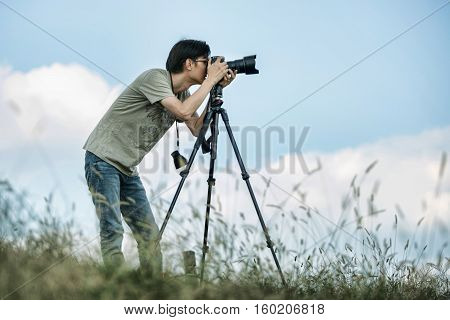 Professional travel on location and nature videographer/photographer (man) photographing nature and landscape outdoor.