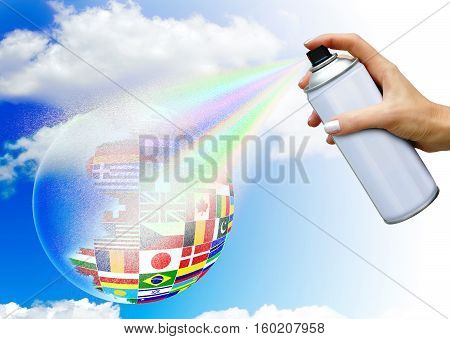 Hand with aerosol spray paints ball in the colors of national flags on sky background. The concept of world community