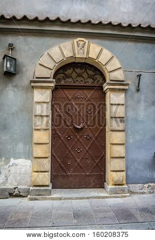 WARSAW POLAND - SEPTEMBER 17: Vintage metal door reinforced with metal belts and rivets and with door knocker in the form of a bird the Warsaw Old Town Poland on September 17 2016