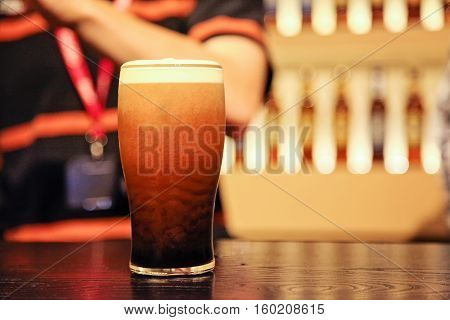 Pint of beer at the counter with male adult person at background