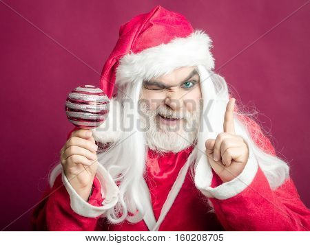 New year man with grimace face has long white beard and hair in red santa claus christmas coat and hat holding decorative ball on studio background