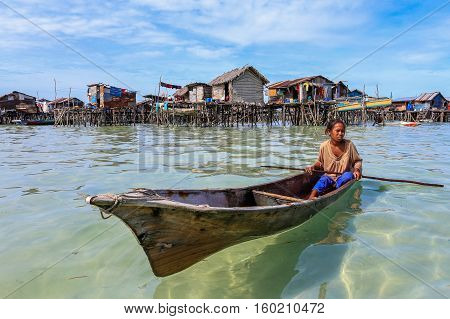 Omadal Island,Semporna,Sabah-Sept 10,2016:Sea Gypsy kid on a boat at Omadal Island,Semporna,Sabah.Sea gypsies kids are given a net & taught to catch fish & octopus off their unique handmade boats