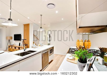 Modern kitchen closeup with white walls and hanging lamps over the counter next to utensils with the stove under the pantry