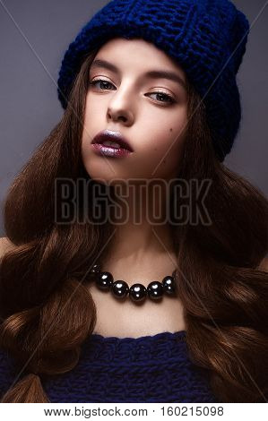 Beautiful woman with bright creative make-up. Model with braids and lip color marsala. Beauty face. The photo was taken in a studio.