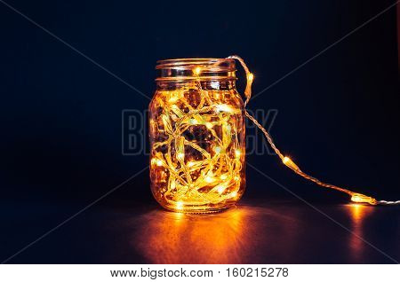 Christmas fairy lights in a mason jar glowing in the dark on a blue background.